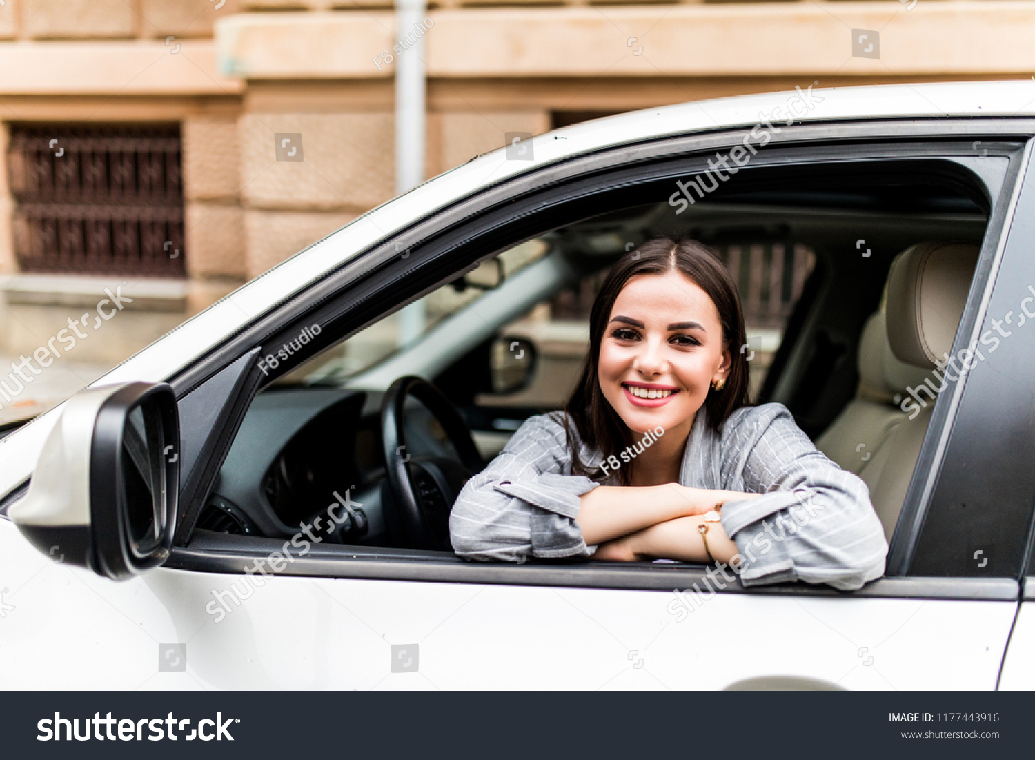 Closeup portrait attractive woman buyer sitting in her new car excited ready for trip isolated outside dealer dealership lot office. Personal transportation auto purchase concept #1177443916