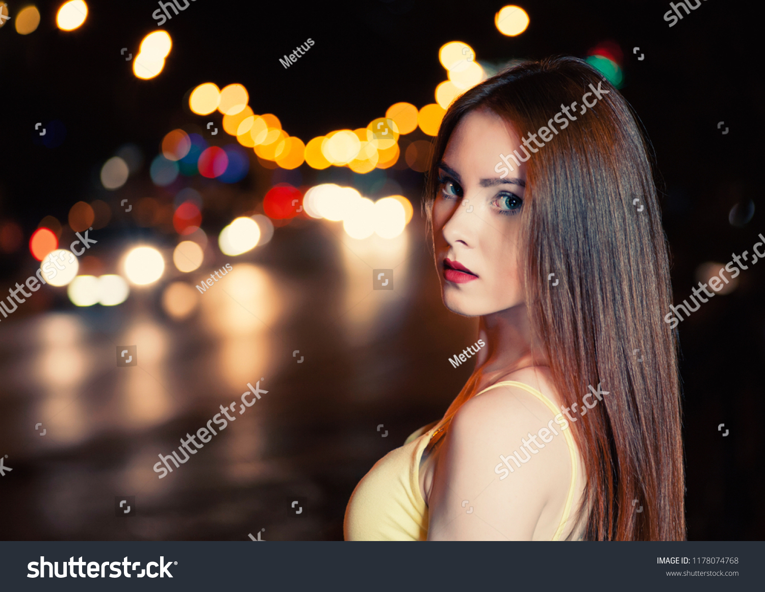 Beautiful girl on blurred carlights background with copyspace. Young women in night street. Defocused carlights.