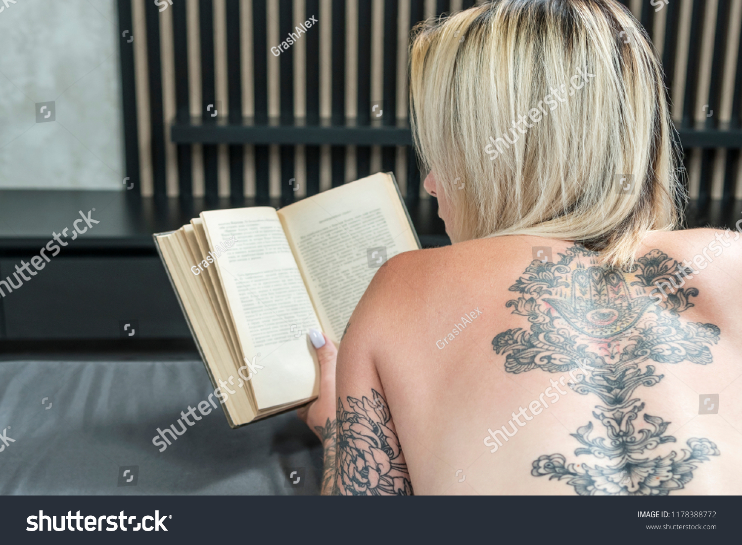 Naked woman with tattoos, reading a book, lying in bed, view from behind