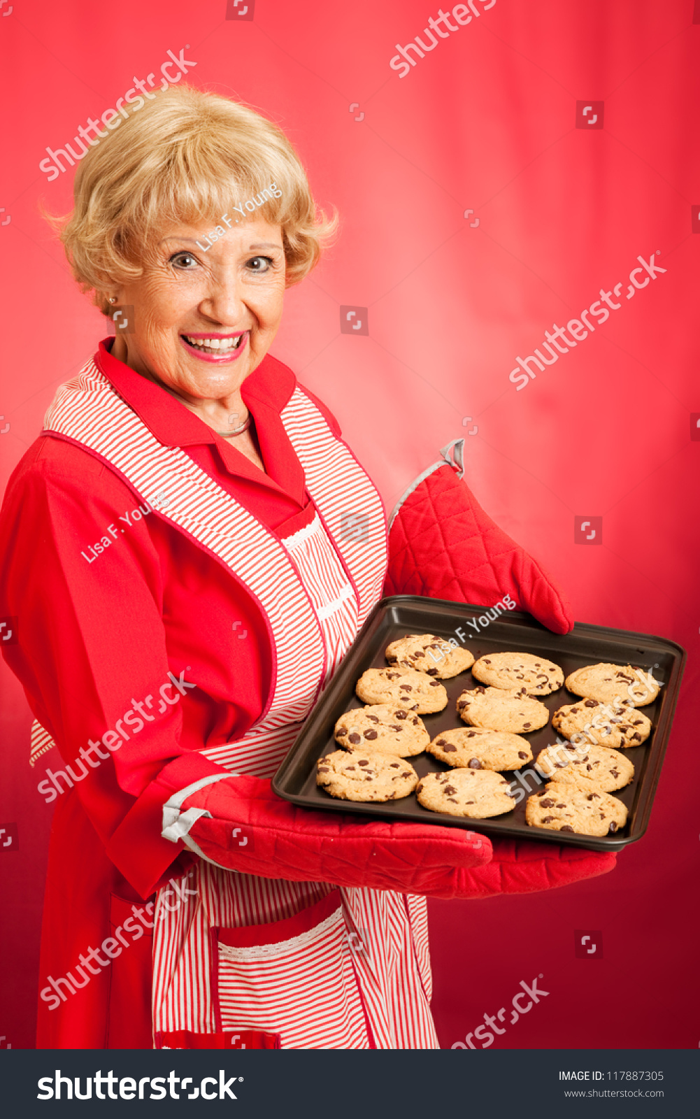 Sweet homemaker grandma holding a tray of fresh baked chocolate chip