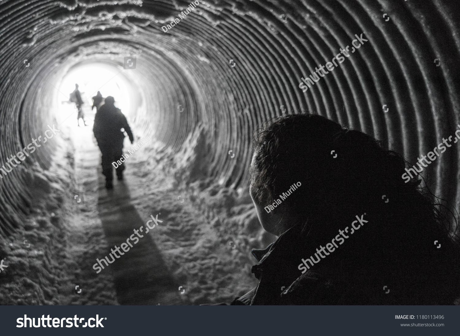 Black and white photo walking through a tunnel towards the light inside a glacier