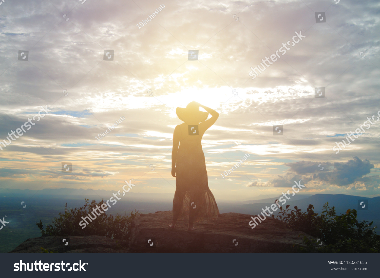 Woman in dress standing alone on mountain top viewpoint looking at sunset behind cloudy sky mountain