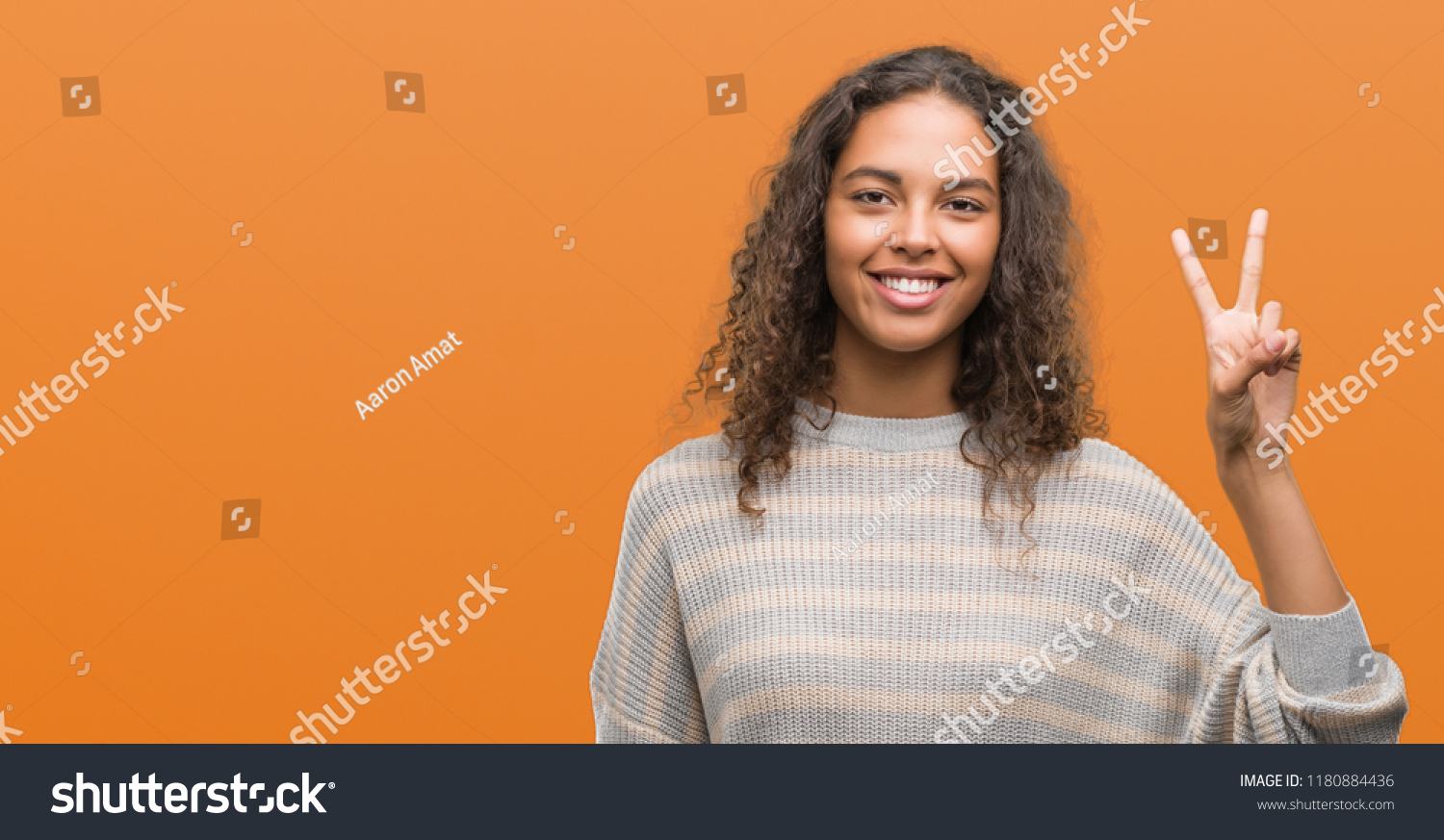 Beautiful young hispanic woman wearing stripes sweater showing and pointing up with fingers number two while smiling confident and happy. #1180884436