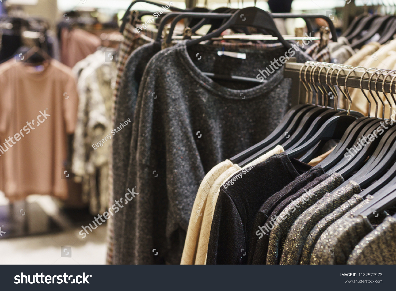 7bed81e65d5 Fashionable men s and women s clothing on wooden hangers in a modern clothing  store. Stylish clothes