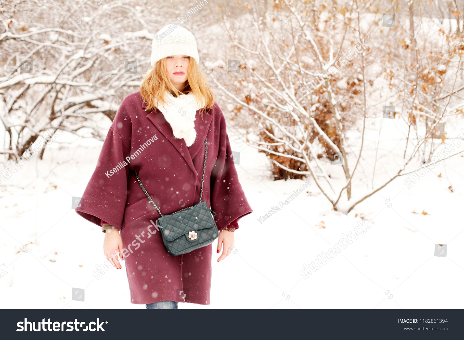 00a8c4a3a3f051 Attractive young woman wearing purple warm coat, white wool knitted cap and  scarf in cold