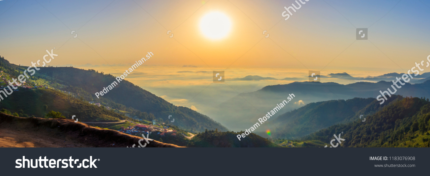Beautiful panoramic landscape above clouds and mountains with sun rising in the middle. #1183076908