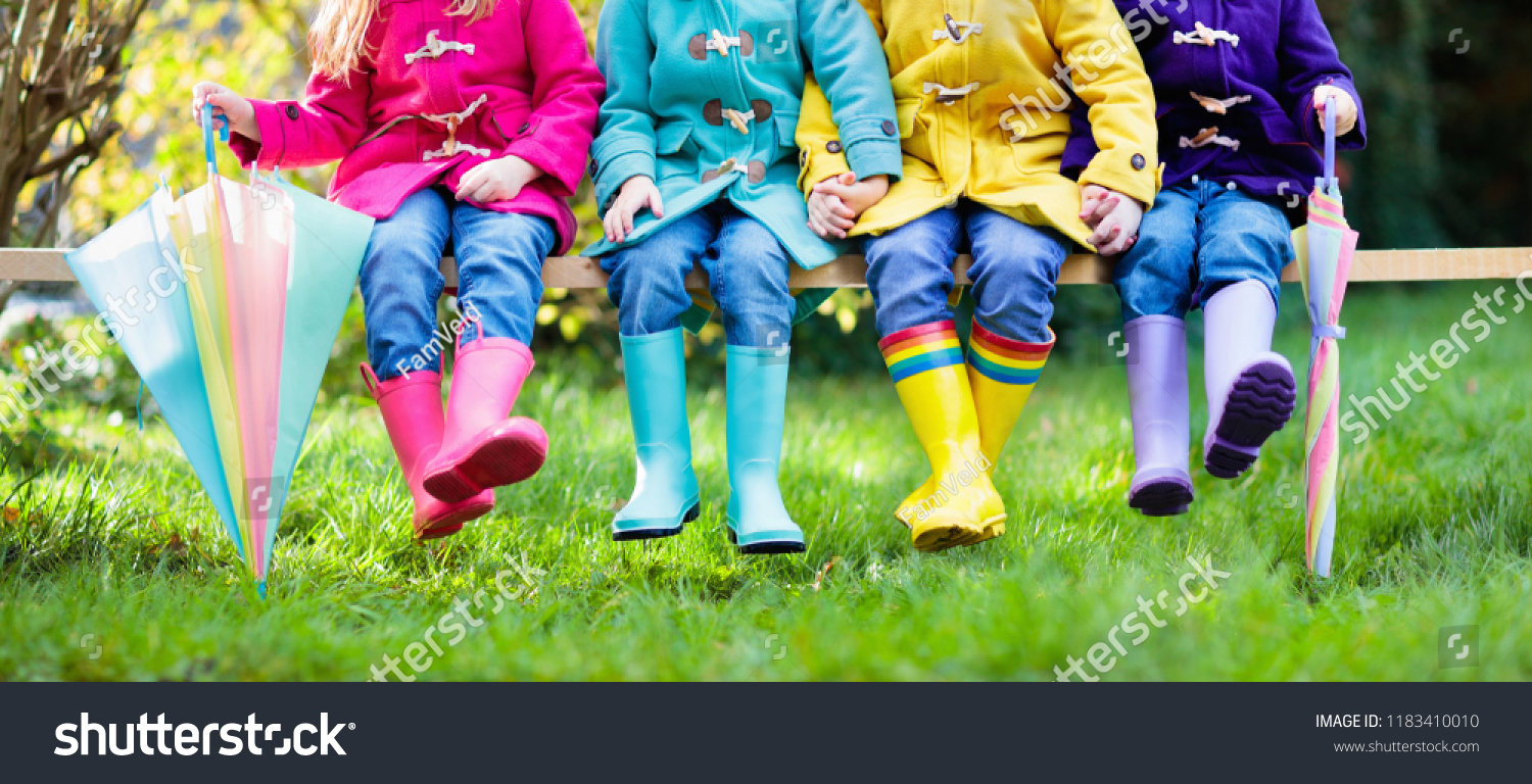 Colorful footwear for children. Boys and girl in rainbow wellies and duffle  coat. Rainbow foot wear and clothing for autumn or winter. Rainy weather ... 6d77d0644e76