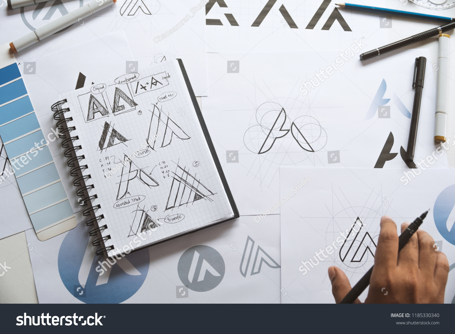 Graphic designer drawing sketch design creative Ideas draft Logo product trademark label brand artwork. Graphic designer studio Concept. #1185330340