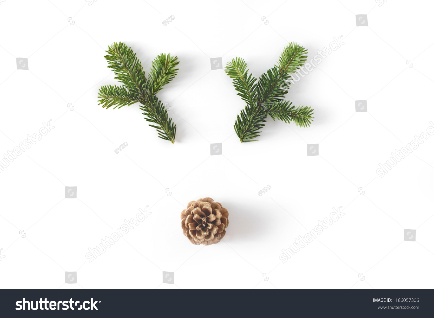 Christmas deer funny face made of fir-tree branches and coniferous cone isolated on white. New year celebration concept. #1186057306
