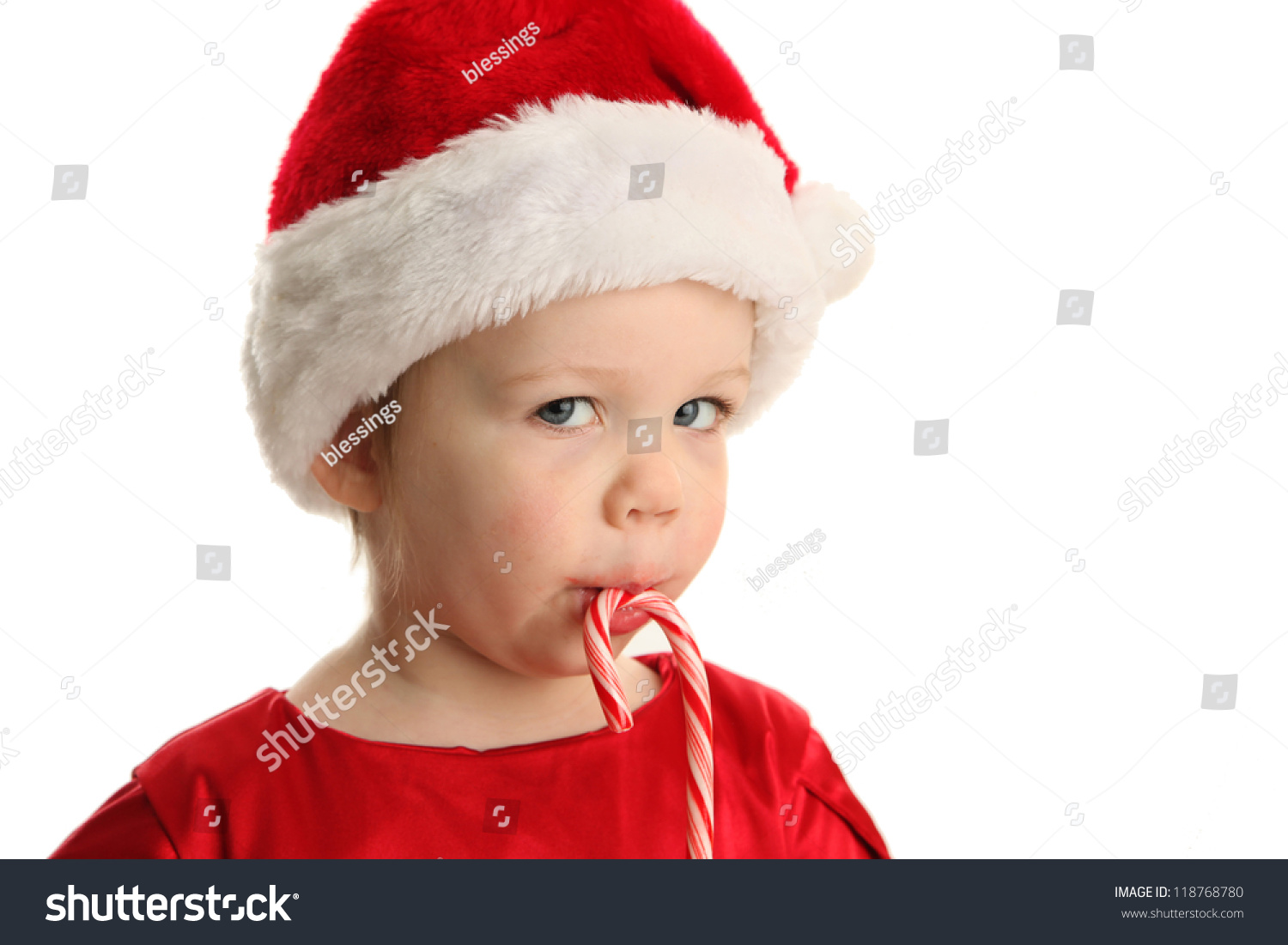 5177ce445c7c2 Christmas Portrait of a beautiful little child girl wearing a santa hat and  holding a candy