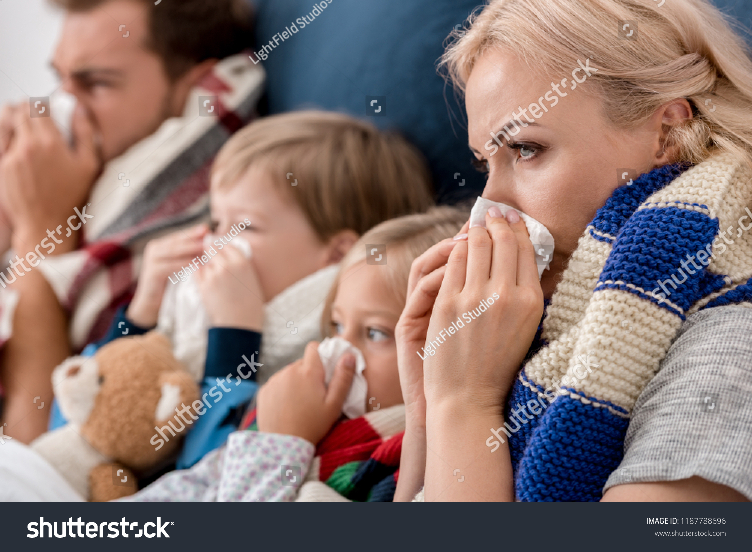 close-up shot of sick young family blowing noses with napkins together while lying in bed #1187788696
