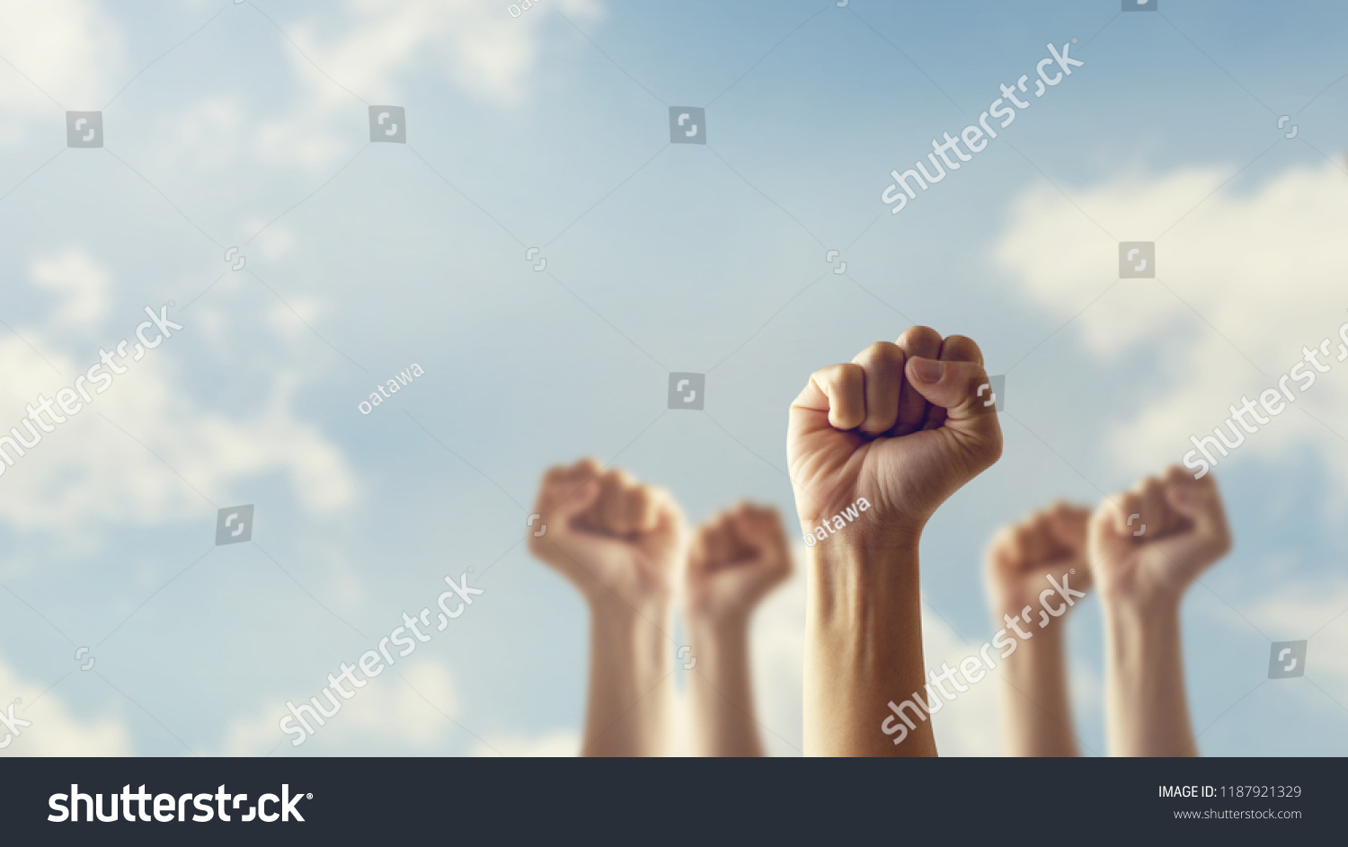 Peoples raised fist air fighting and sunlight effect, Competition, teamwork concept, background space for text. #1187921329
