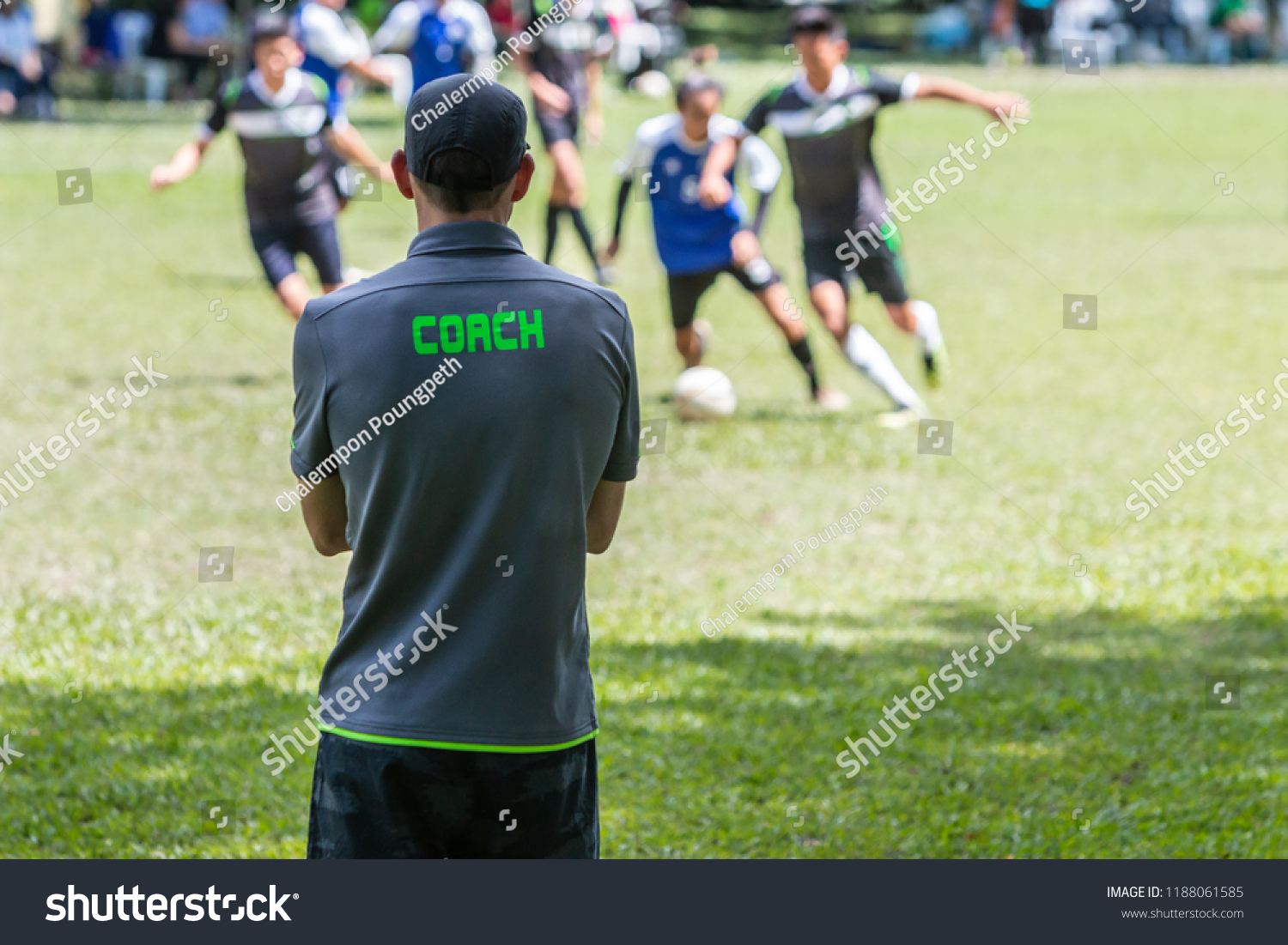 ecbc4d507 Male soccer or football coach in gray shirt with word COACH written on  back, standing on the sideline watching his team play, good for sport or  coaching ...