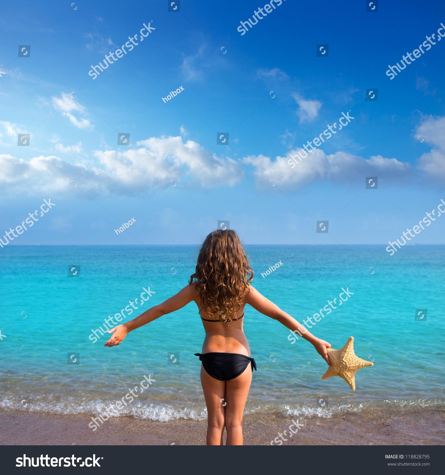 preeteens bikini blue beach kid girl with bikini holding starfish looking sea in rear view