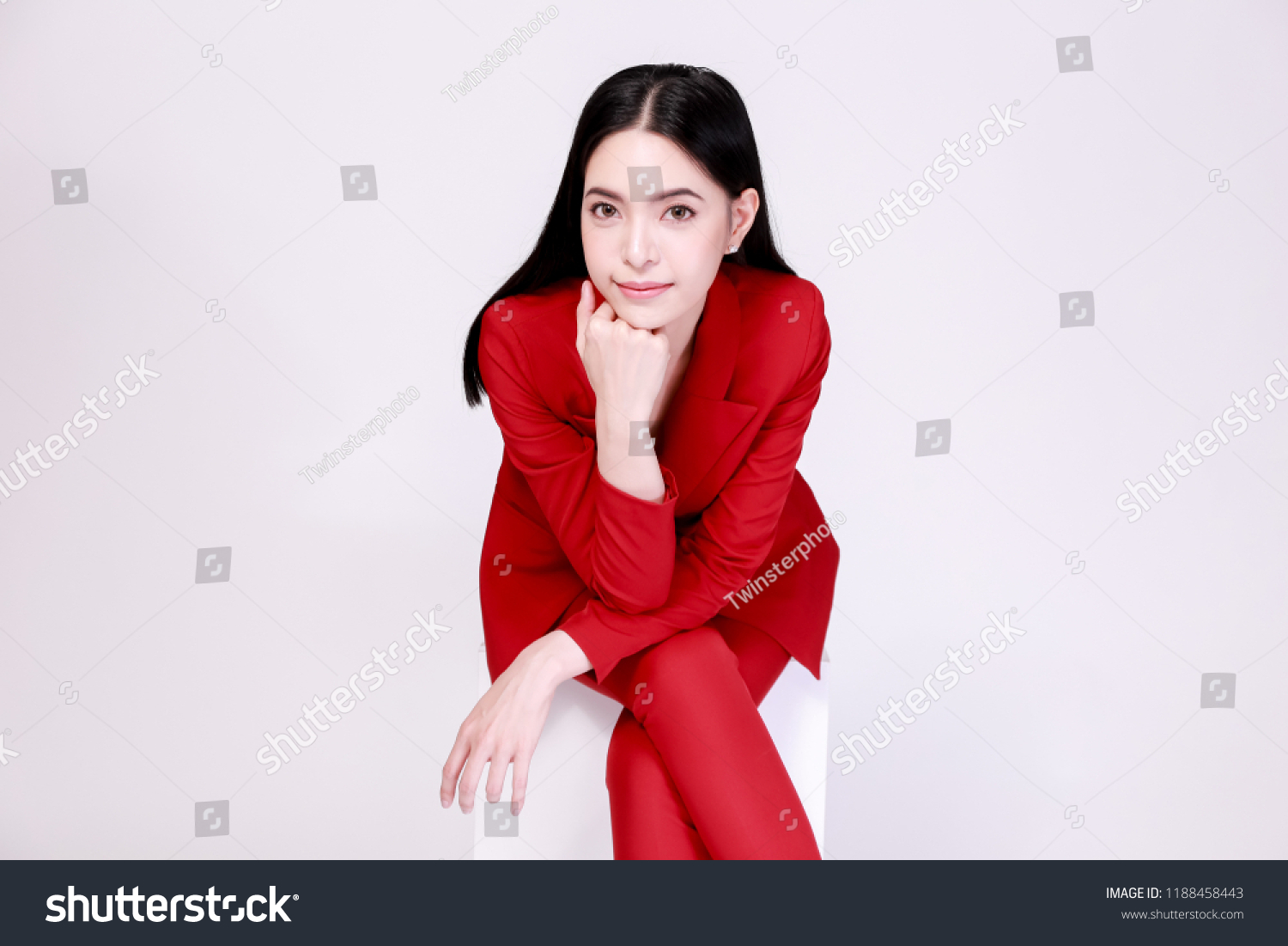 8d09c45e7fd Young confident Asian woman in red elegant suit with pants posing sitting  in half body isolated