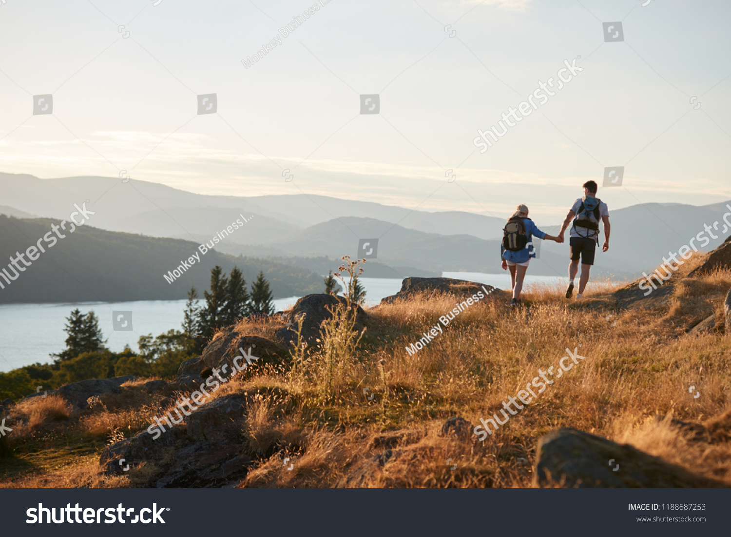 Rear View Of Couple Walking On Top Of Hill On Hike Through Countryside In Lake District UK #1188687253