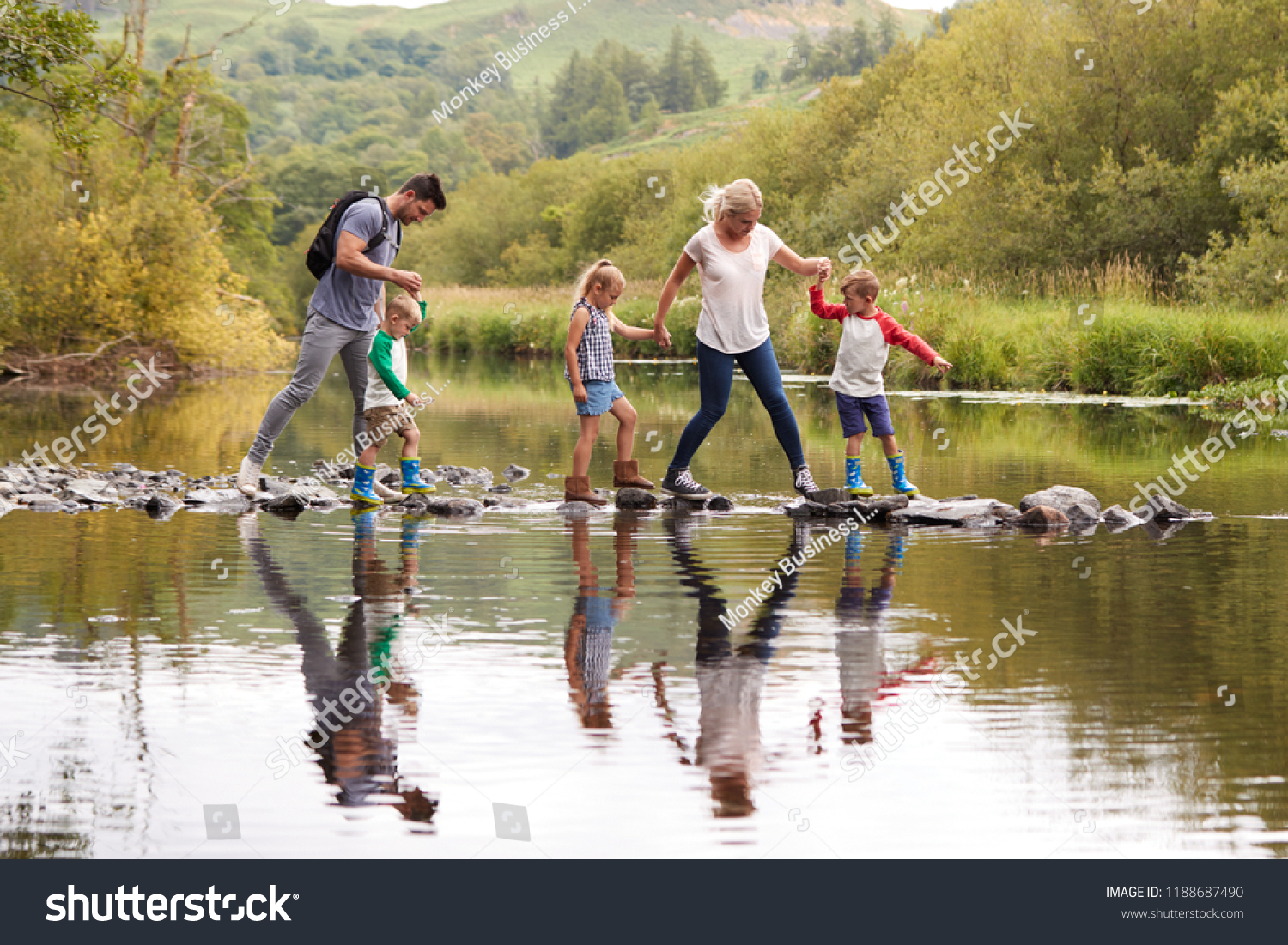 Family Crossing River Whilst Hiking In UK Lake District #1188687490