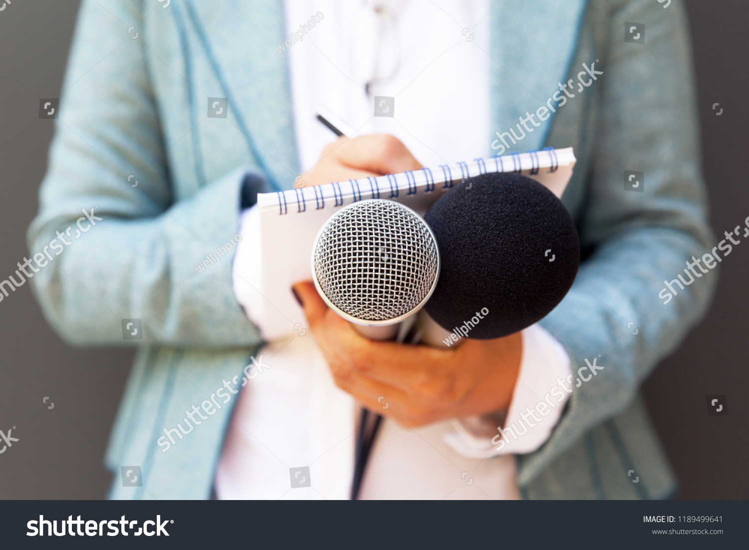 Female reporter at press conference, writing notes, holding microphone #1189499641