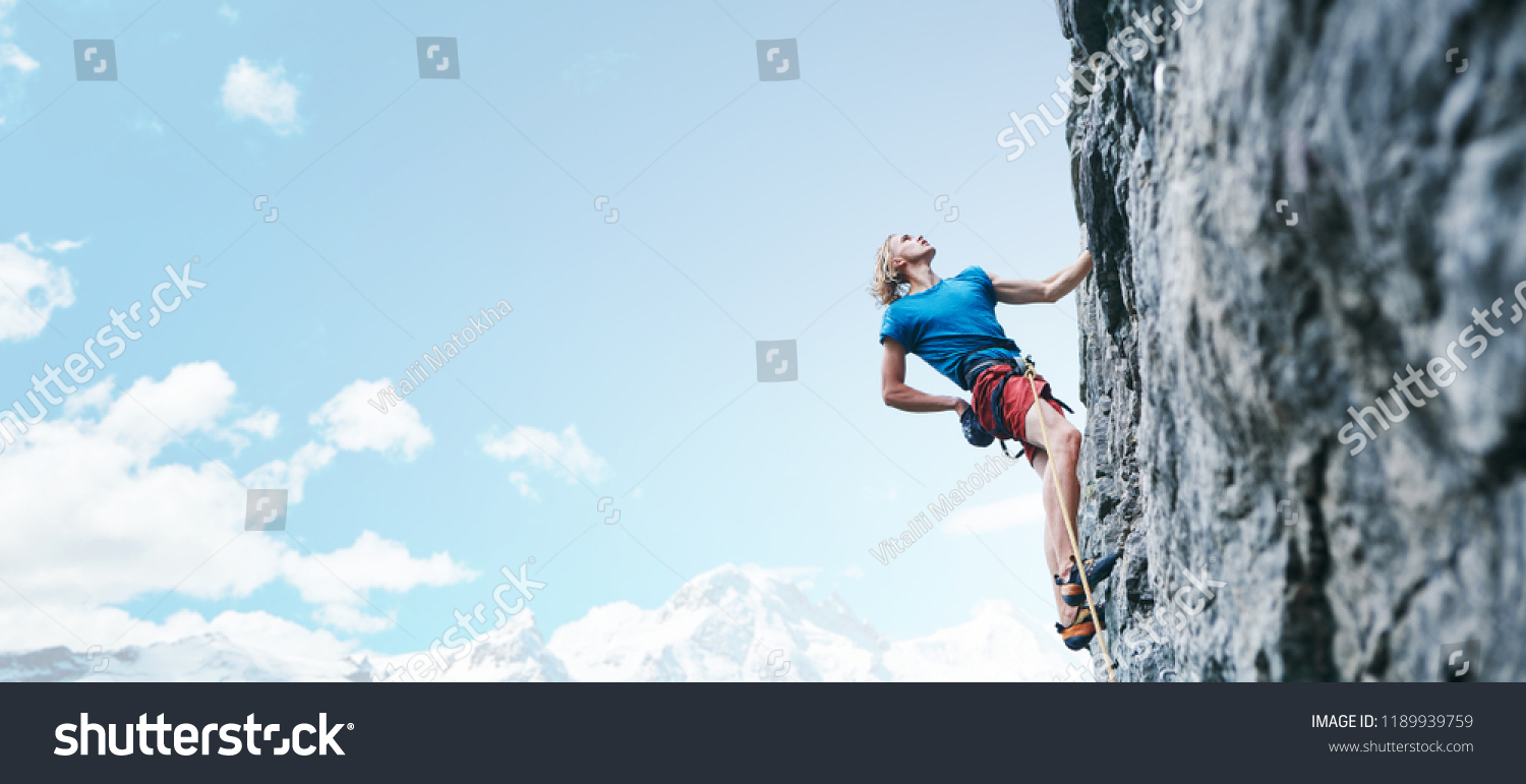 man rock climber with long hair. side view of young man rock climber in bright red shorts climbing the challenging route on the cliff on the blue sky background. rock climber climbs on a rocky wall. #1189939759