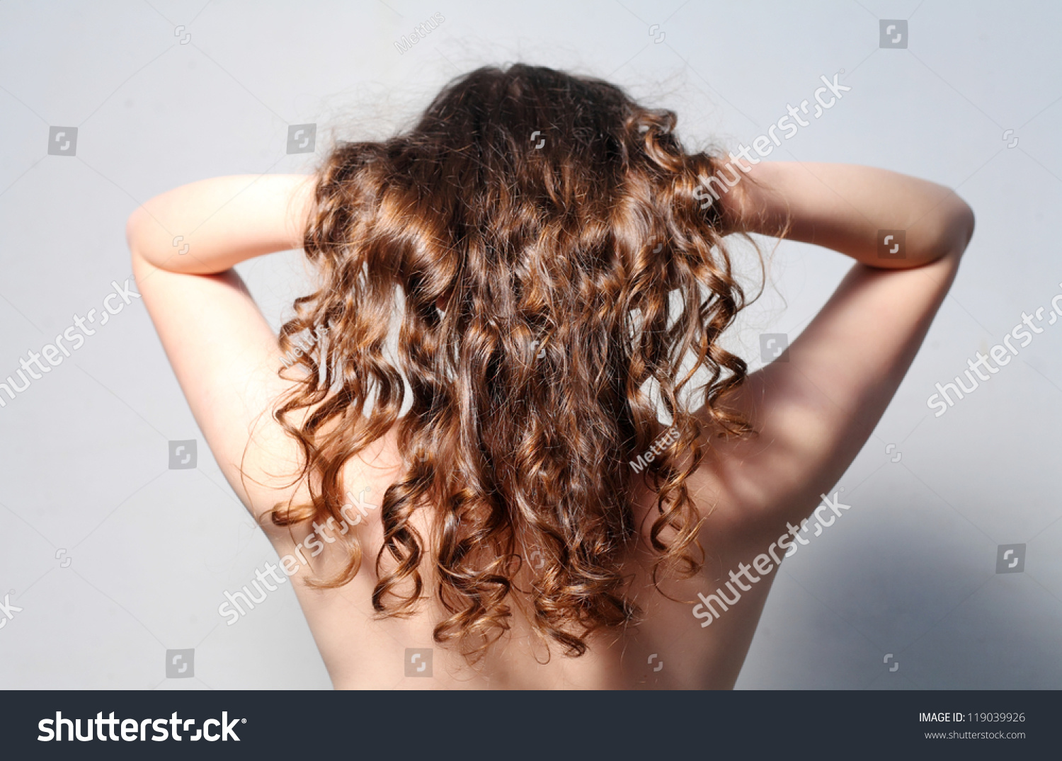 Topless lady posing with her curly red hairs lifted up in hands - rear view shot.