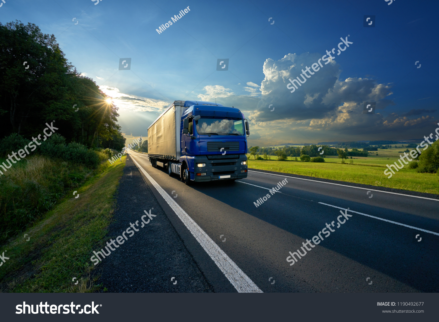 Blue truck arriving on the asphalt road in rural landscape in the rays of the sunset                                #1190492677