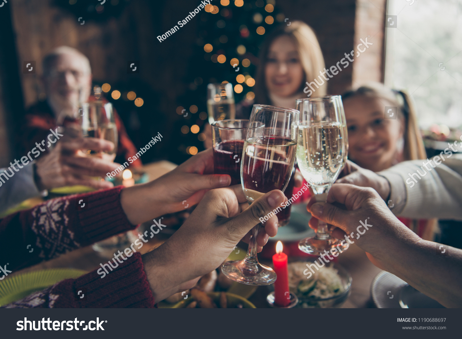 Eve family gathering meeting dream wish concept. Cropped wineglass, cheerful gray-haired grandparents, grandchildren, daughter sitting at table, house party, fun joy navidad hands hold glass #1190688697