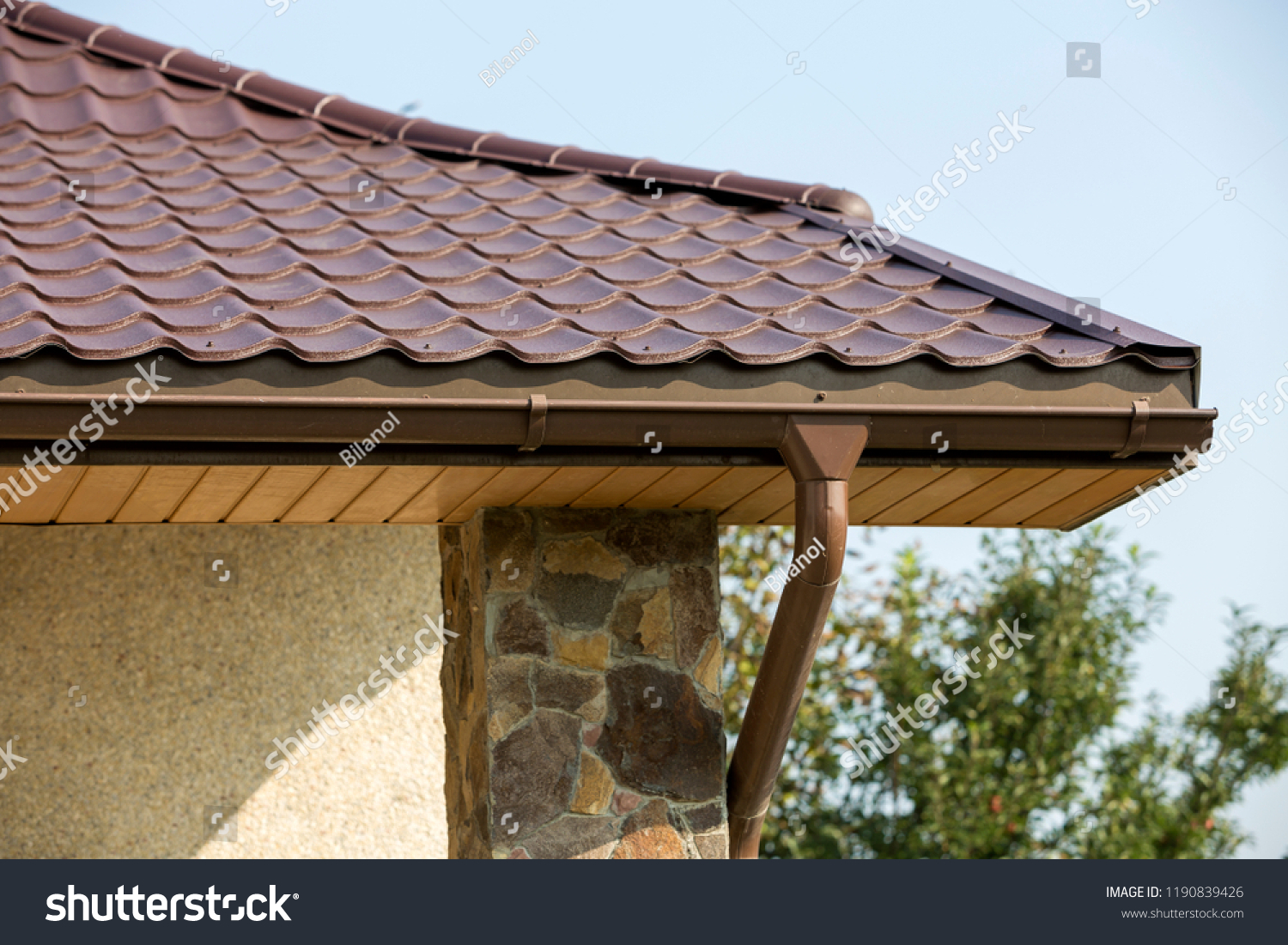 Detail of new modern house cottage corner with stucco walls decorated with natural stones brown
