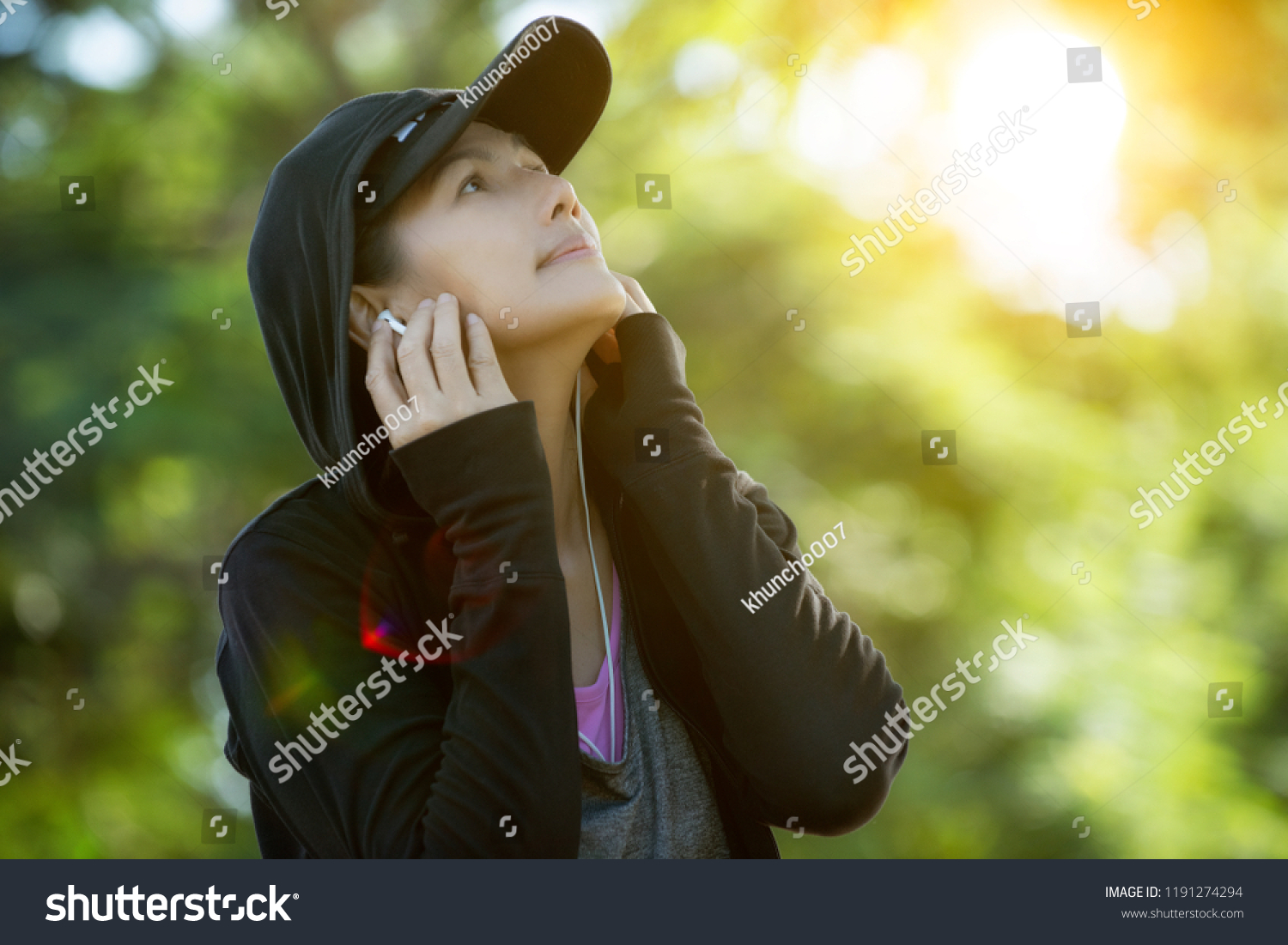 Young joyful woman asian sitting alone in a park and listening to music on earphones