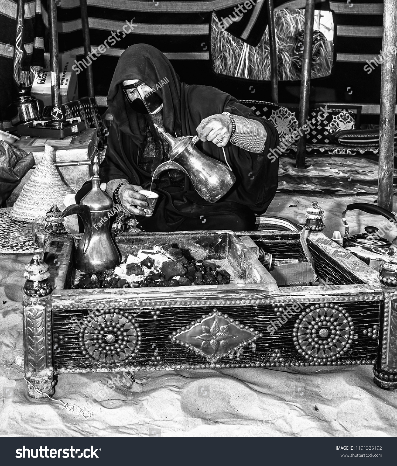 Black and white photography photographed on 23 11 2017 abu dhabi uae a woman offers arabic coffee to sheikh zayed heritage festival visitors image