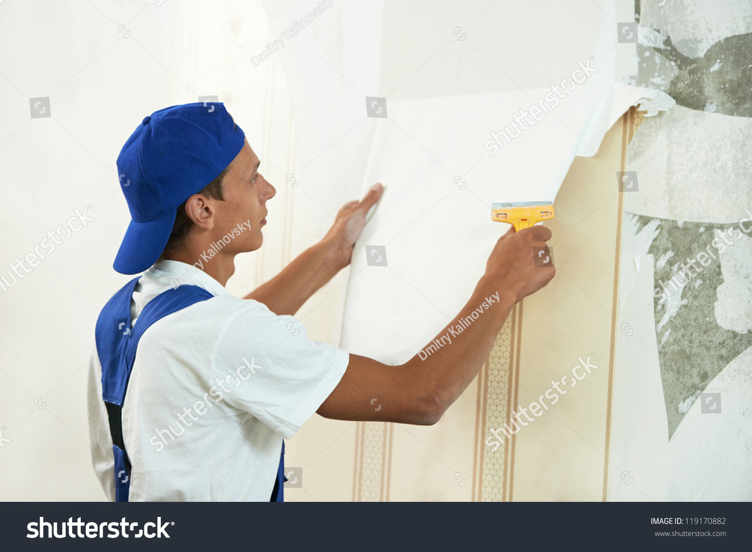 One painter worker peeling off wallpaper stock photo for Wallpaper home improvement questions