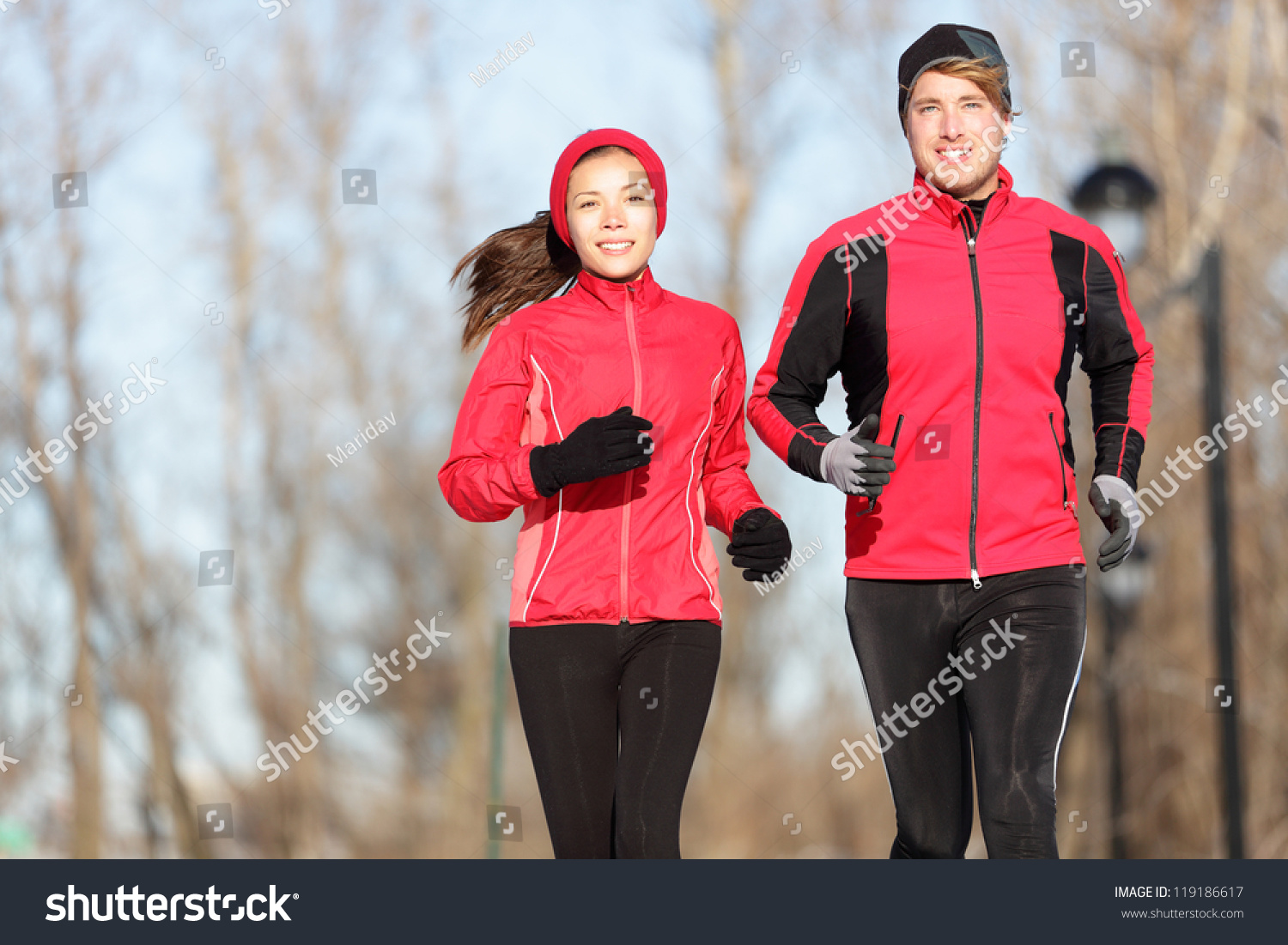 Running. Runners jogging outside. Young couple training outside in warm sport clothing outfit.