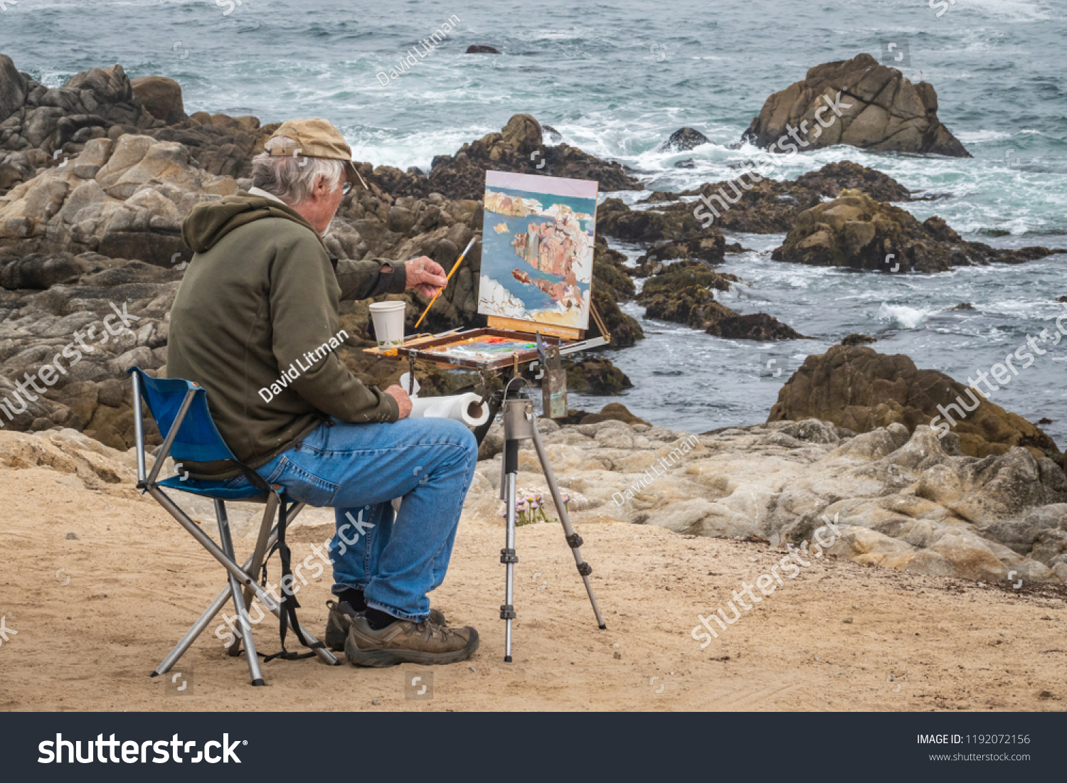 Pacific Grove, California - September 19, 2018: An artist sits along a seaside bluff at Asilomar Beach, along the Pacific Coast of central California, while painting the rocky coastline below.