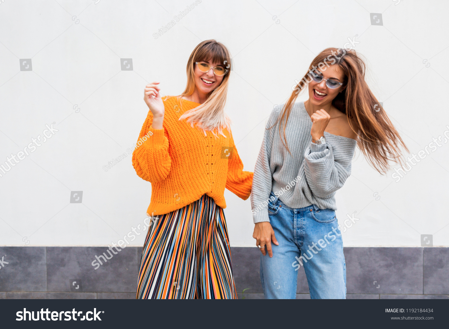 7a834537675 Outdoor lifestyle portrait of couple of young women having fun together.  Windy hairs. Two