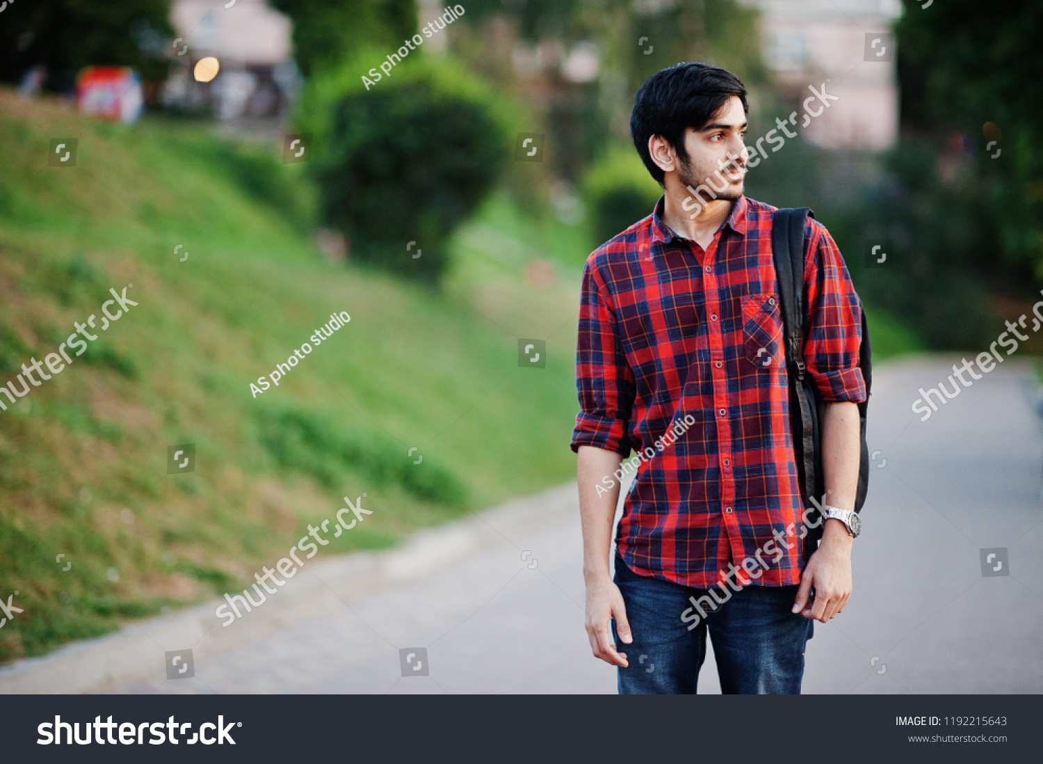 ea70a74a89 Young indian student man at red checkered shirt and jeans with backpack  posed at street.