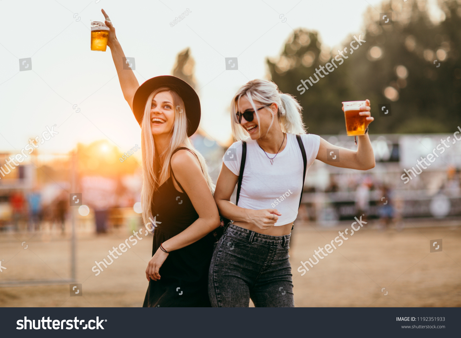 Two female friends drinking beer and having fun at music festival #1192351933