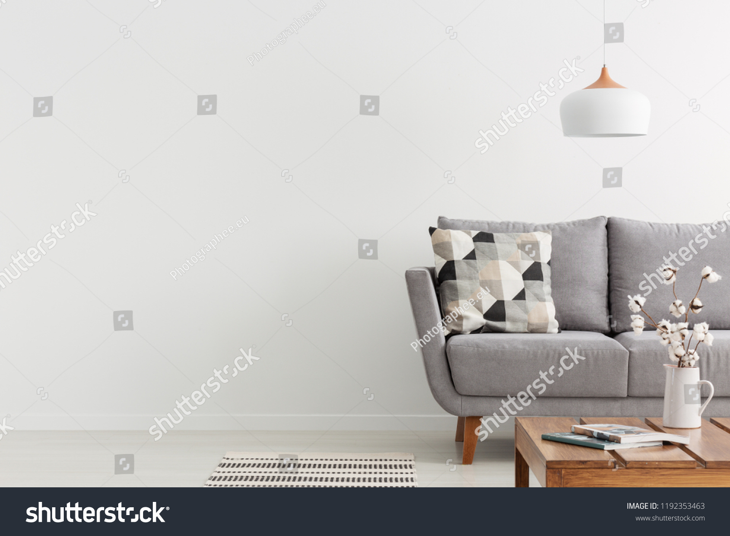 Flowers on wooden table and grey settee in white living room interior with copy space. Real photo #1192353463