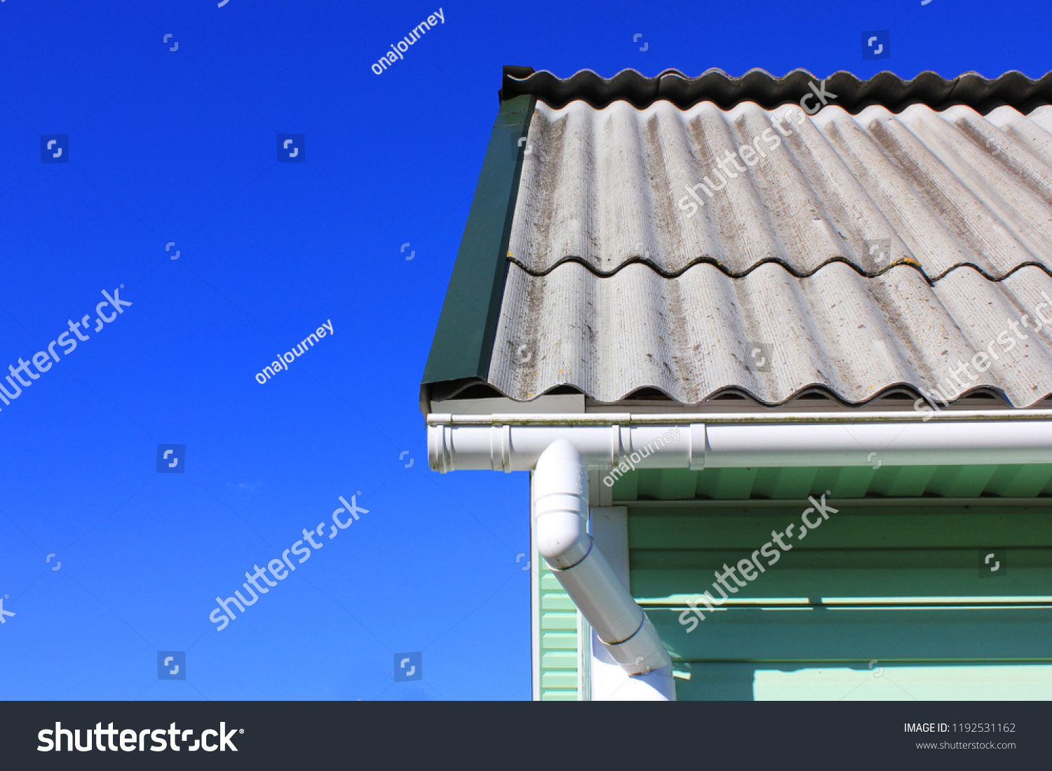 House corner with gutter roof top tiles drainage system and azure wall detail on