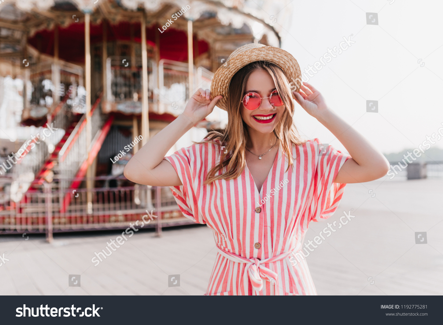 f51d3110120 Spectacular female model with sincere smile posing near carousel in  amusement park. Joyful white young