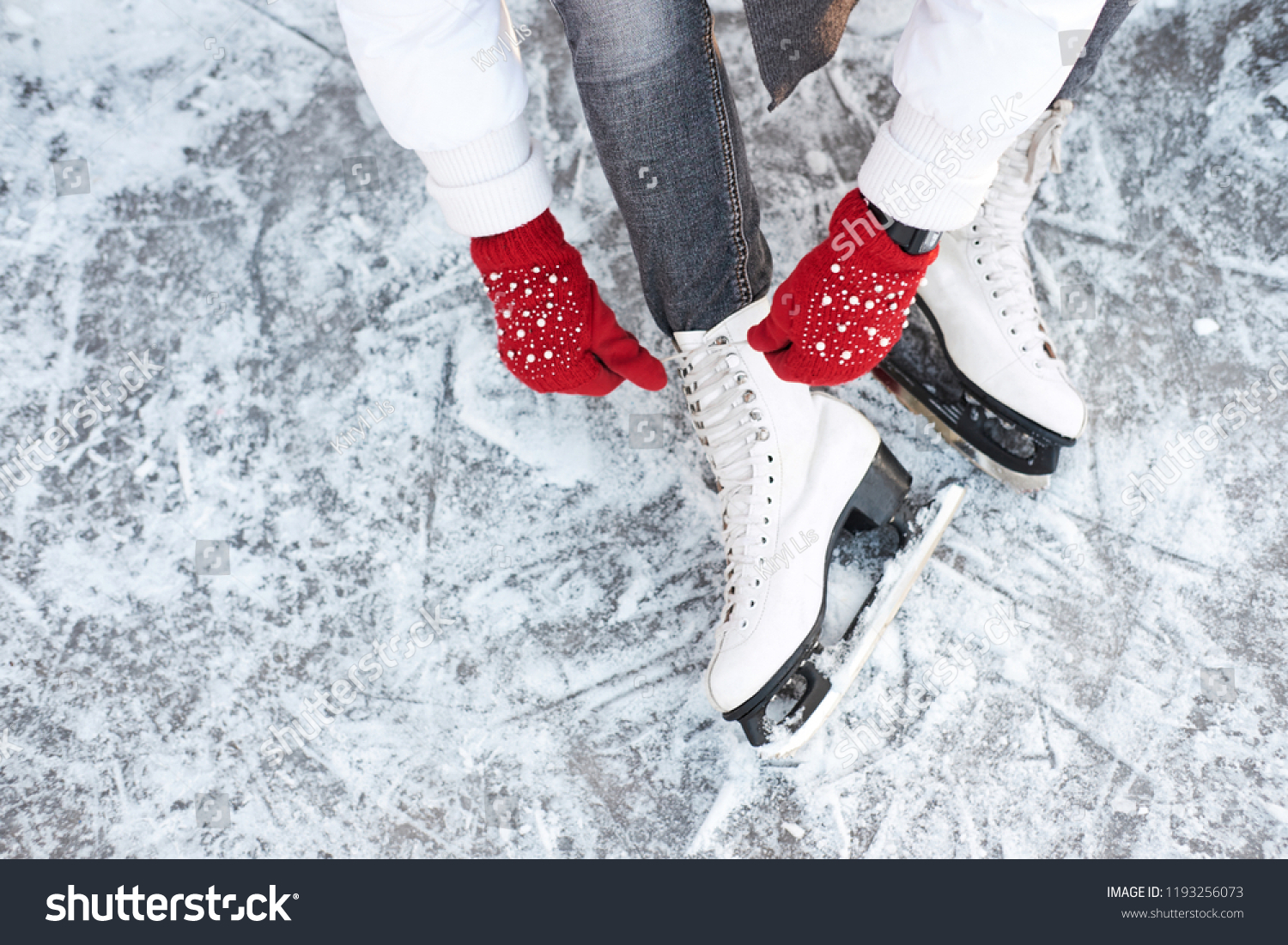 Girl tying shoelaces on ice skates before skating on the ice rink, hands in red knitted gloves. View from top. #1193256073