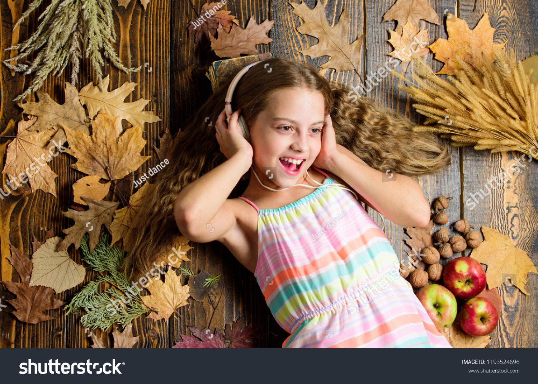 Kid listen music headphones wooden background child listen music relaxing top view fall melody