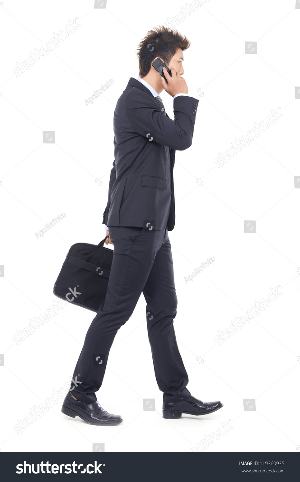 stock-photo-full-body-young-business-man-walking-carrying-a-suitcase-speaking-on-cellphone-119360935.jpg