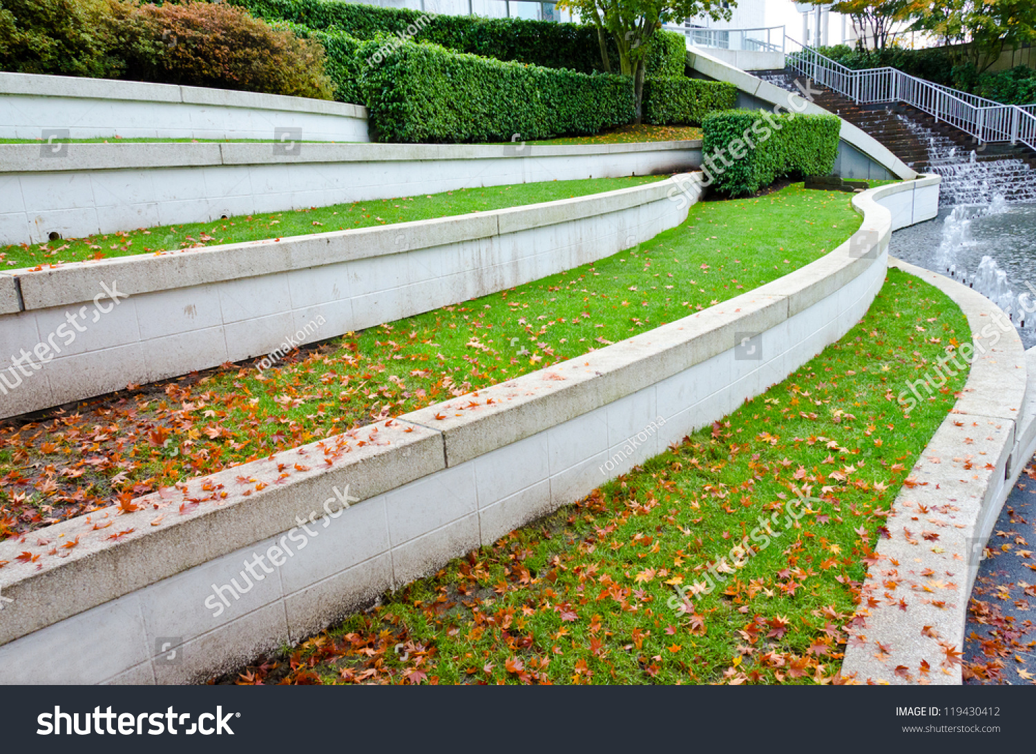Leveled terraces with grass and fountains in a city plaza for Landscape design canada
