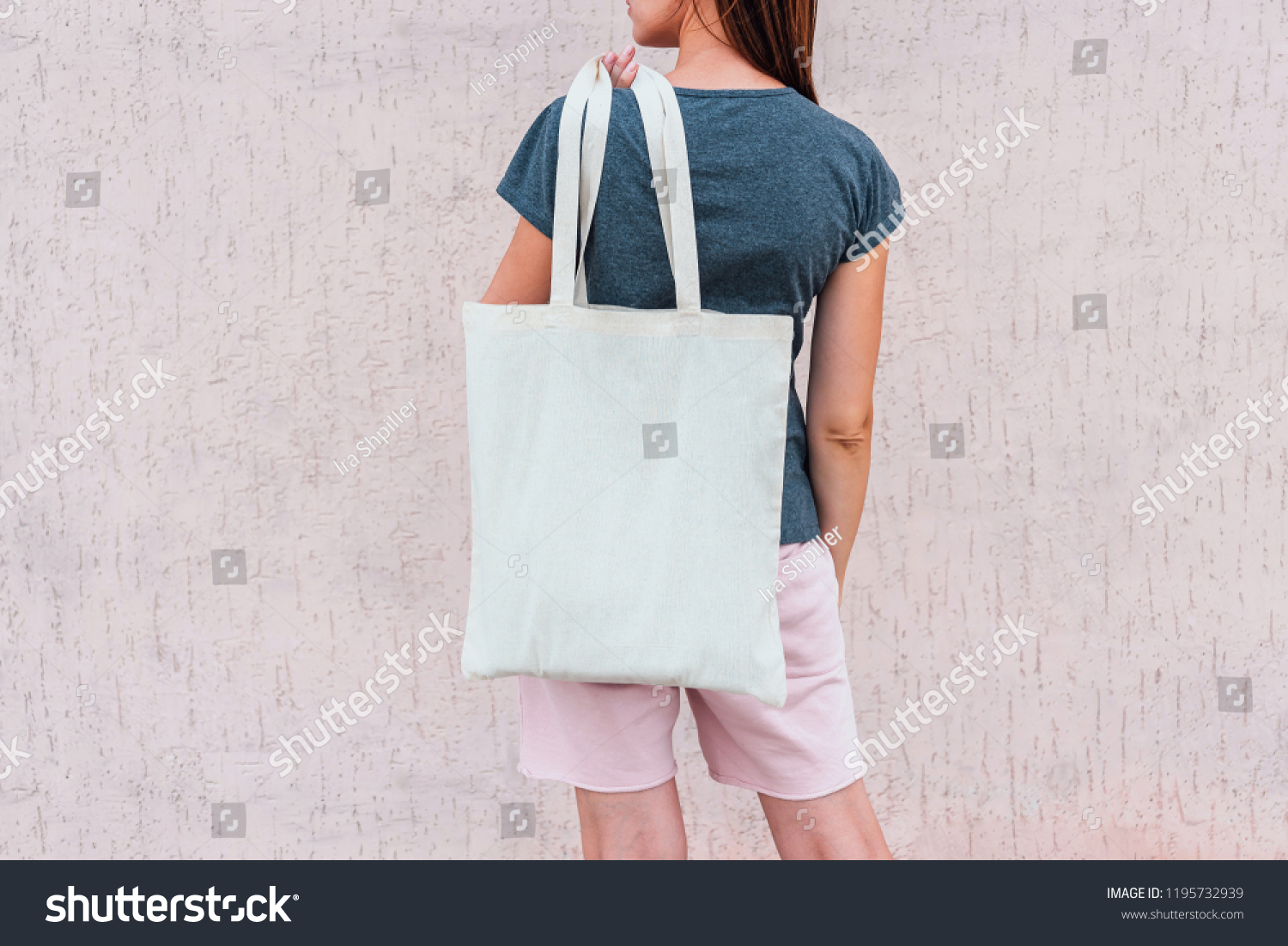 Young woman with white cotton bag in her hands.