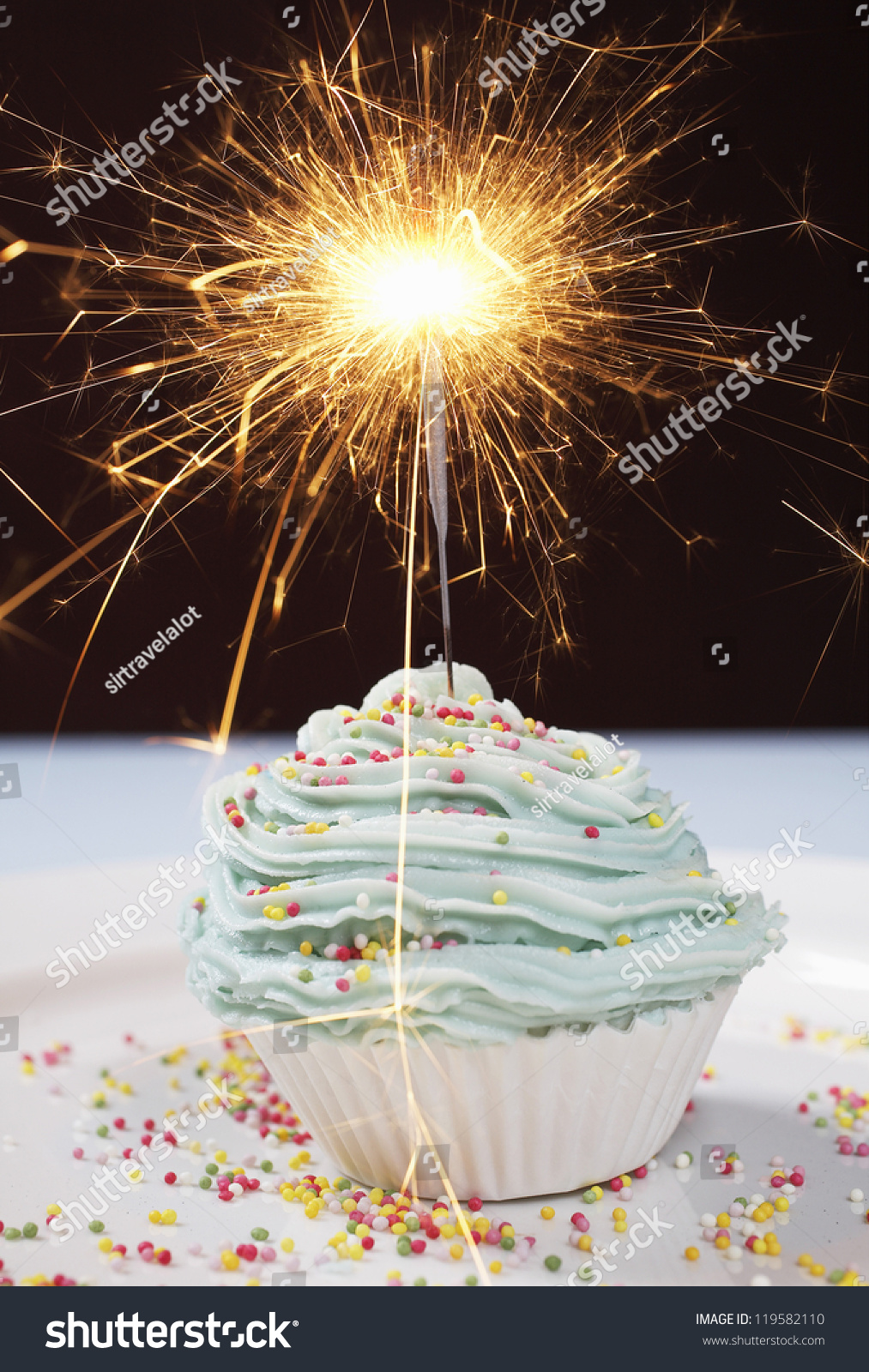 Baked Cupcake On Table With Sparkling Candle Isolated Over Black Background
