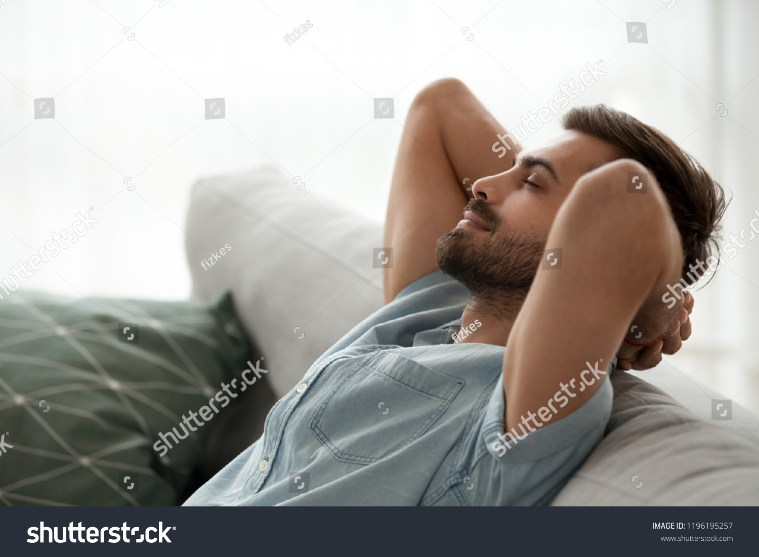 Close up side view serene man smiling sitting on couch at home. Male has a break after work or study closing eyes putting hands behind head relaxing thinking, feels happy breathing fresh air concept #1196195257