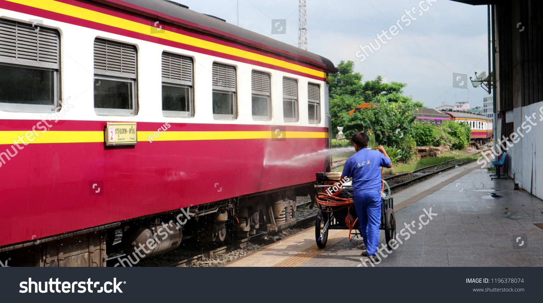 BANGKOK, THAILAND - OCTOBER 6, 2018: An Employee water hose a railway passenger car at Hua Lamphong train station on October 6, 2018 in Bangkok, Thailand.