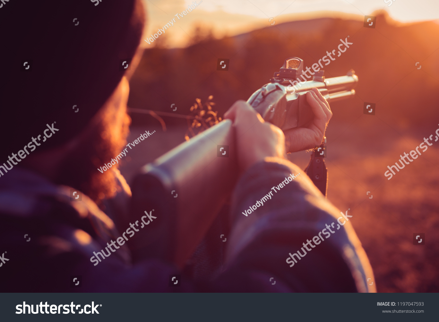 Close up snipers carbine at the outdoor hunting. Rifle Hunter Silhouetted  in Beautiful Sunset.