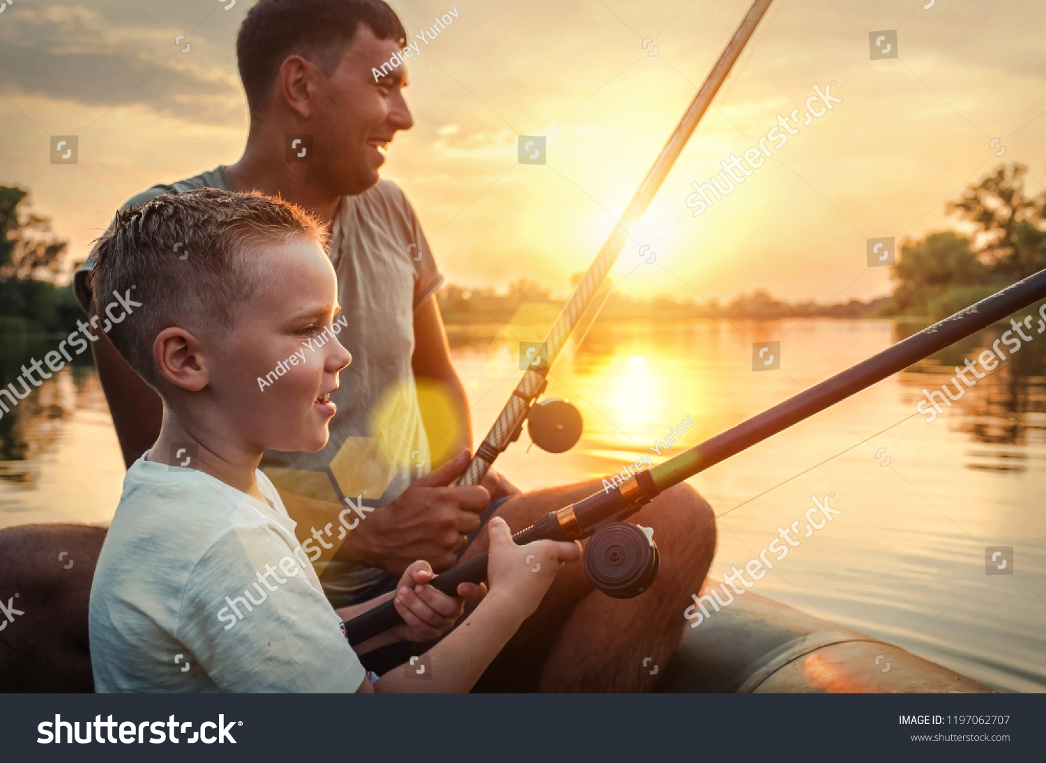 Happy Father and Son together fishing from a boat at sunset time in summer day under beautiful sky on the lake. #1197062707