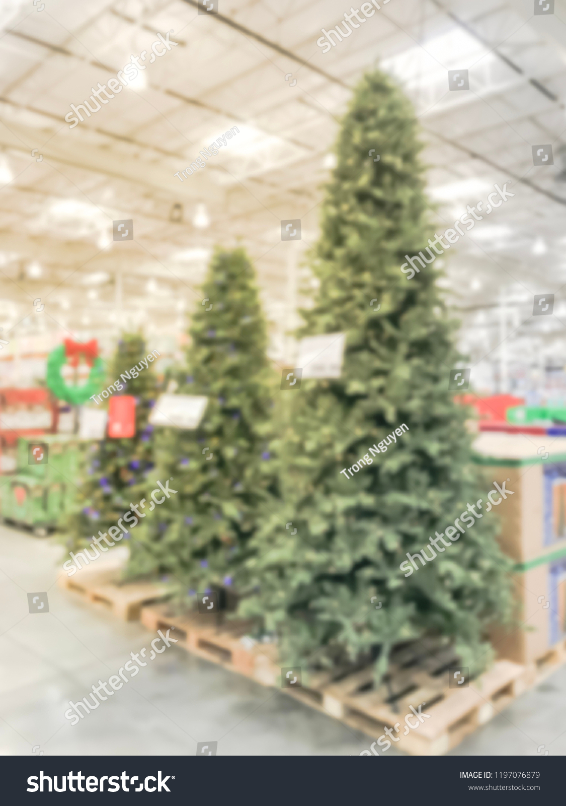 Motion blurred tall and big Christmas trees decoration at wholesale store.  Wreaths and strings of