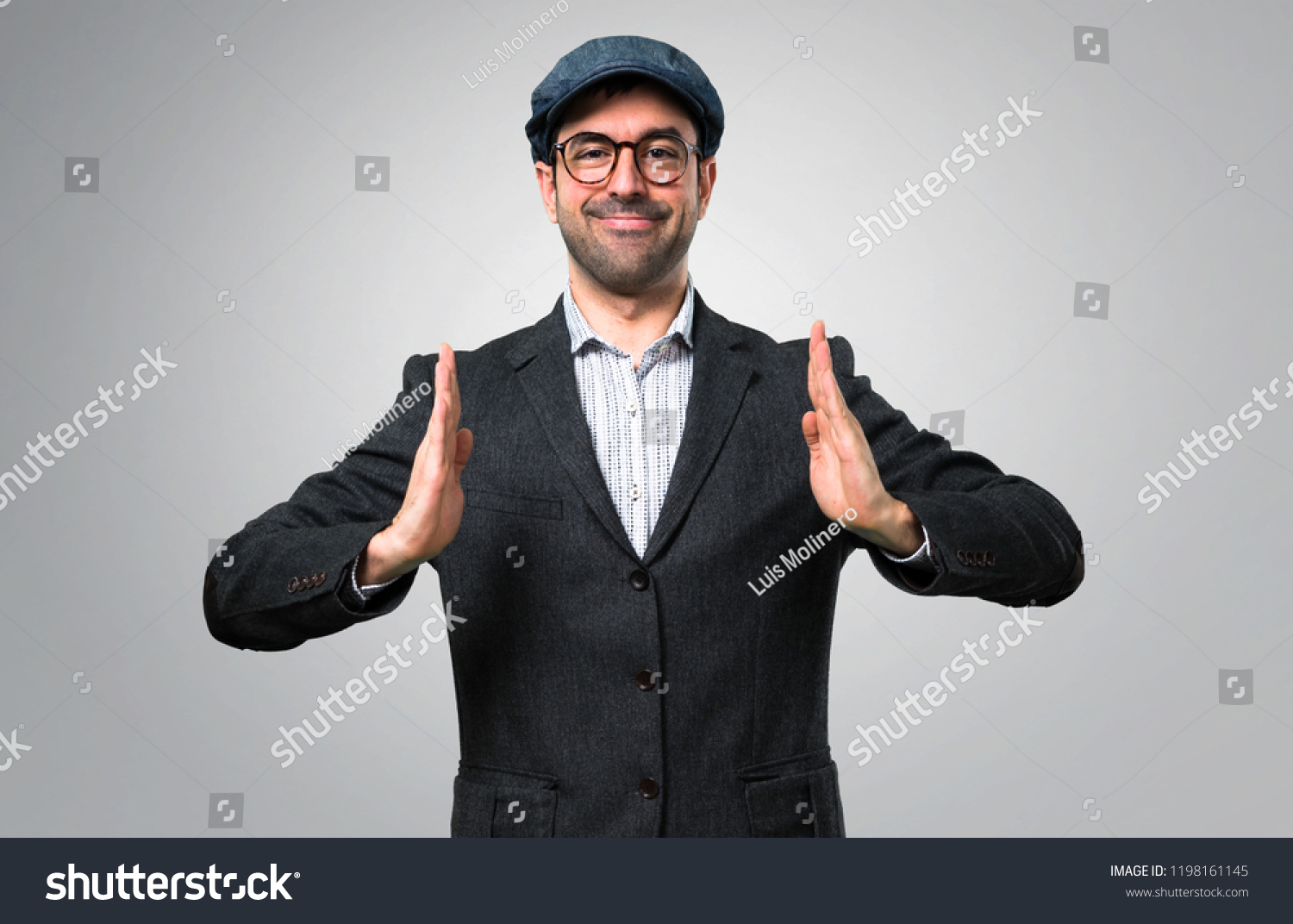 24e198eb1b17f Handsome modern man with beret and glasses holding copyspace imaginary on  the palm on grey background